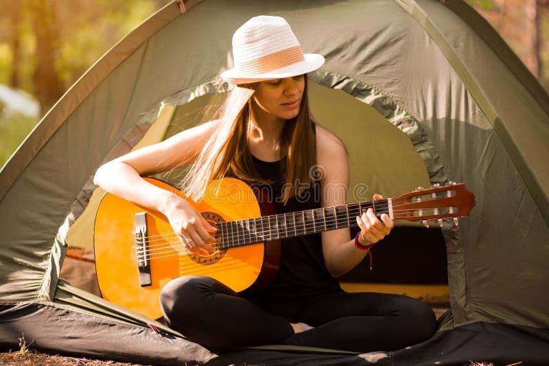 Turystyczna dziewczyna w kapeluszu siedzi w namiocie i bawi? si? gitary poj?cie Turystyka odpoczynek na naturze obrazy royalty free
