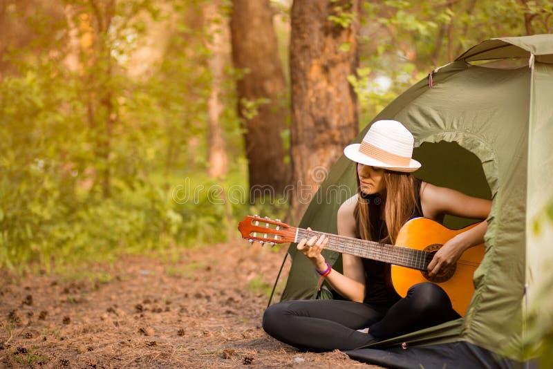 Turystyczna dziewczyna w kapeluszu siedzi w namiocie i bawi? si? gitary poj?cie Turystyka odpoczynek na naturze zdjęcie royalty free