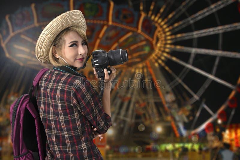Turystyczna dziewczyna z parkiem rozrywkim w nocy na tle zdjęcie royalty free