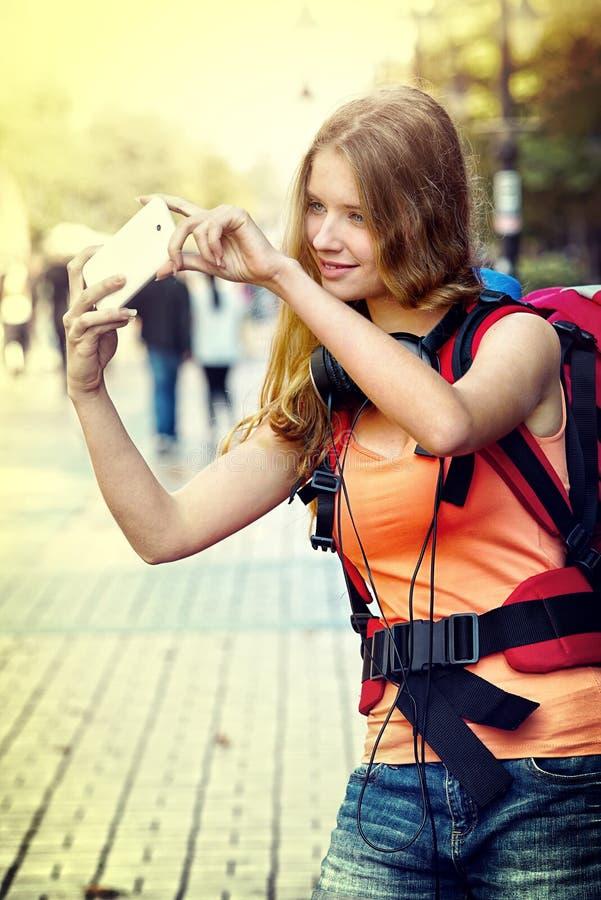Turystyczna dziewczyna z plecakiem bierze selfies na smartphone zdjęcia stock
