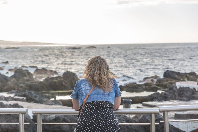 Turystyczna kobieta obserwuje morze podczas gdy odpoczywający na poręczu zdjęcie royalty free