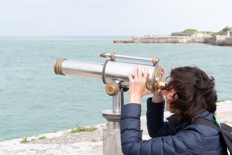 Turystyczna kobieta patrzeje przez moneta działać lornetek na morze wakacje obrazy royalty free