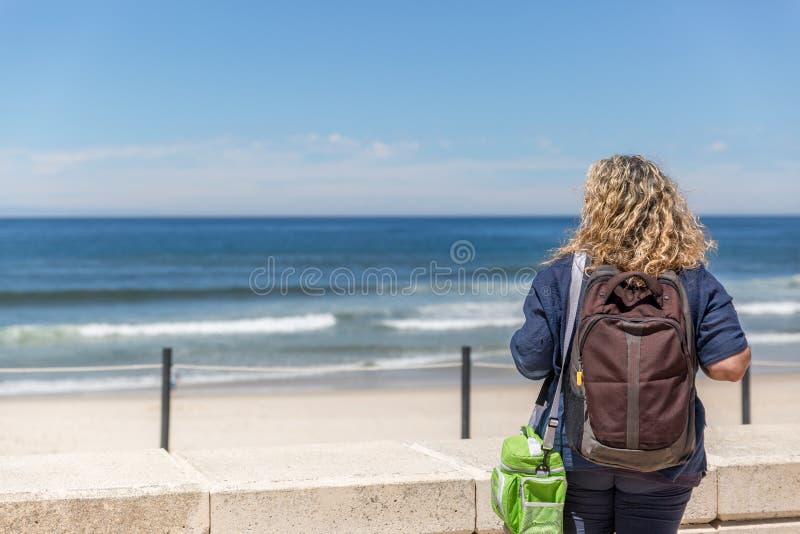 Turystyczna kobieta, placidly obserwuje pla?? na s?onecznym dniu zdjęcia stock