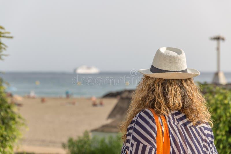 Turystyczna kobieta z kapeluszem, placidly obserwuje plażę z ludźmi obrazy stock