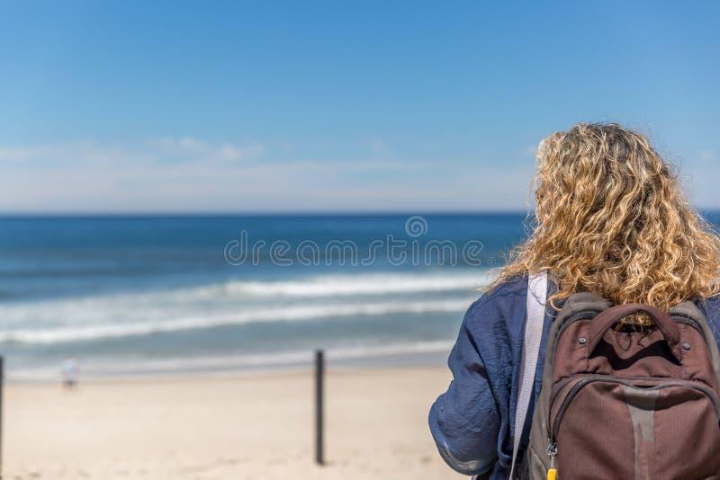Turystyczna kobieta z plecakiem na ona z powrotem, placidly obserwuje spokojnego morze na plaży na słonecznym dniu, obraz stock