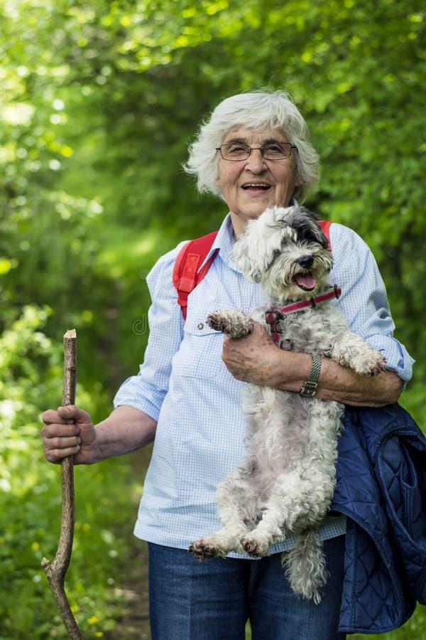 Turystyczna Starsza kobieta z jej psem w górze obrazy royalty free