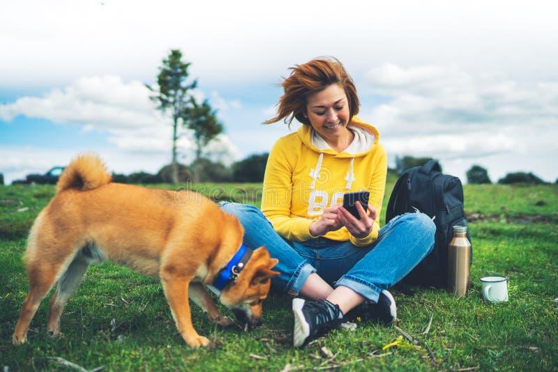 Turystyczna uśmiech dziewczyna na tło natury krajobrazowym używa mobilnym smartphone z przyjaciółmi psy, osoby mienie w ręka gadż zdjęcia royalty free
