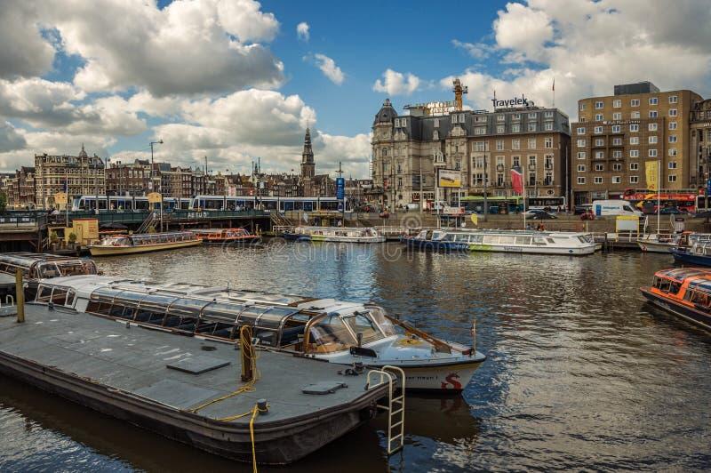 Turystyczne łodzie i most na szerokim kanale w słonecznym dniu przy Amsterdam zdjęcie stock