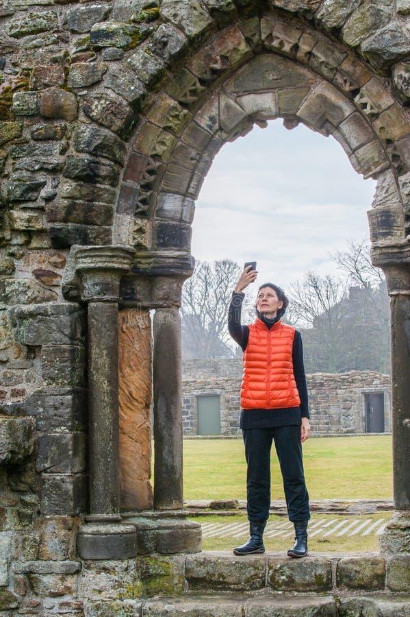 Turystyczne kobiety bierze selfie obrazki ruiny St Andrews fotografia royalty free