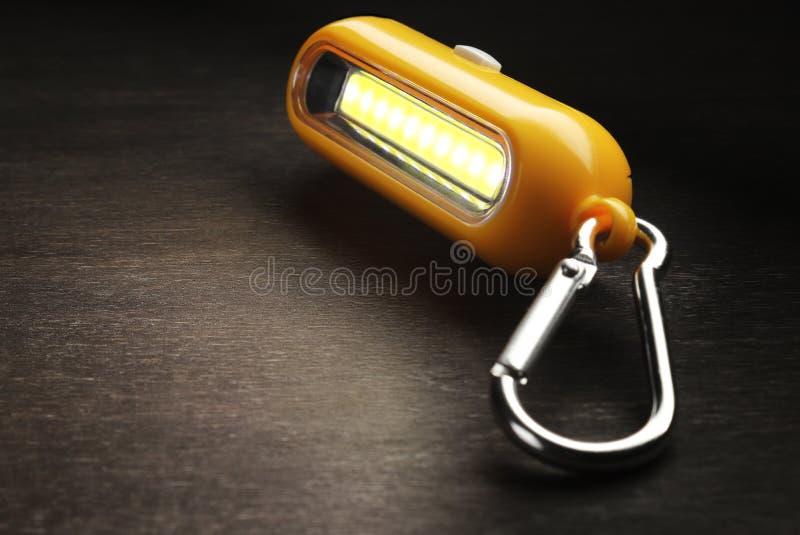 Turystycznej latarki kluczowy łańcuch z carabiners na drewnianym tle zdjęcie stock