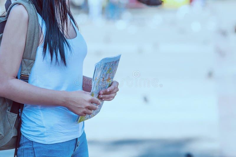 Turystycznej podróży kobieta patrzeje mapę podczas gdy chodzący na ulicie obrazy royalty free