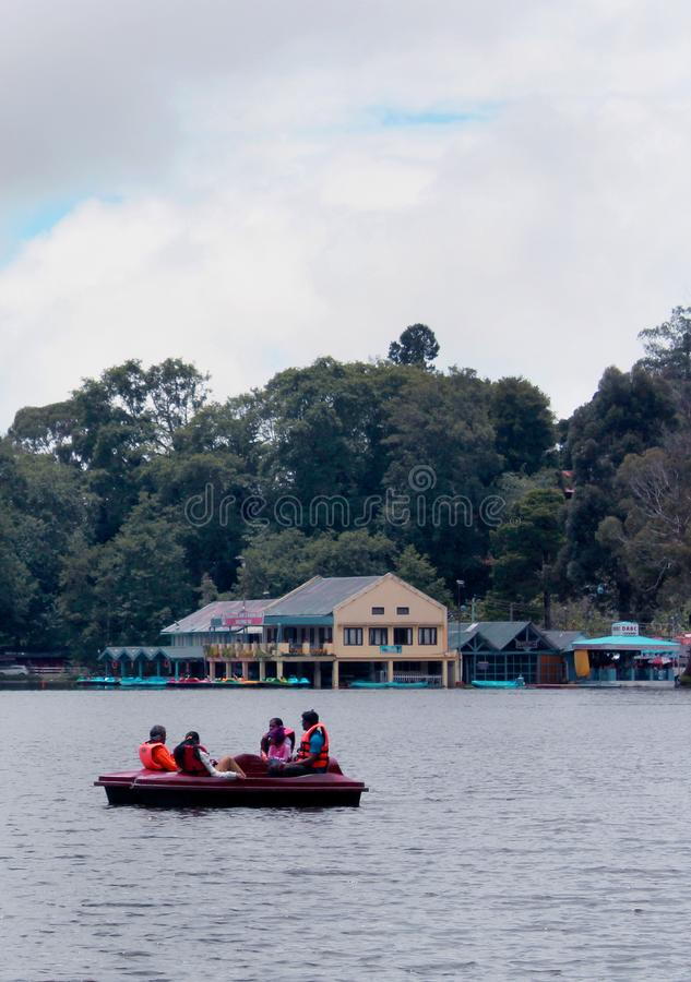 Turystyczni ludzie wodniactwo przy kodaikanal jeziornym pobliskim łódkowatym domem fotografia stock