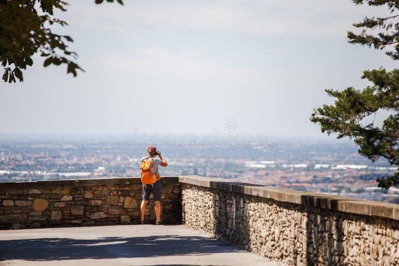 Turystyczni mężczyzna stojaki z jego plecy na viewing platformie w Bergamo w Włochy i biorą fotografię na kamerze jest ubranym sk zdjęcie royalty free