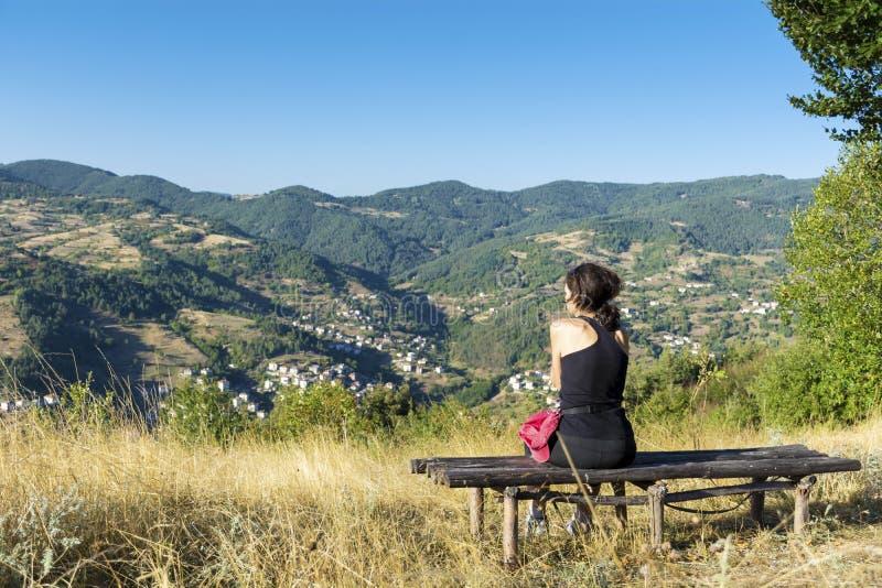 Turystyczny kobiety obsiadanie na drewnianej ławce w wysokiej jesieni górze zdjęcie royalty free