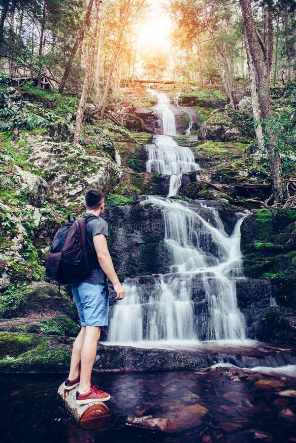 Turystyczny mężczyzna stoi blisko siklawy w górach i cieszy się widok fotografia royalty free