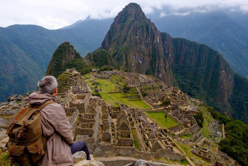 Turystyczny obsiadanie na jego plecy ogląda Mach Picchu Gubił miasto inka zdjęcia royalty free