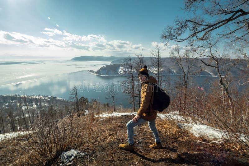 Turystyczny podróżnik z plecaków stojakami na górze i spojrzeniami przy pięknym widokiem jeziorny Baikal Styczeń 33c krajobrazu R obraz stock