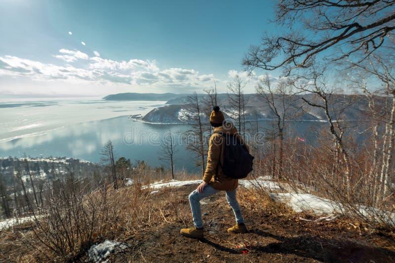 Turystyczny podróżnik z plecaków stojakami na górze i spojrzeniami przy pięknym widokiem jeziorny Baikal Styczeń 33c krajobrazu R fotografia stock
