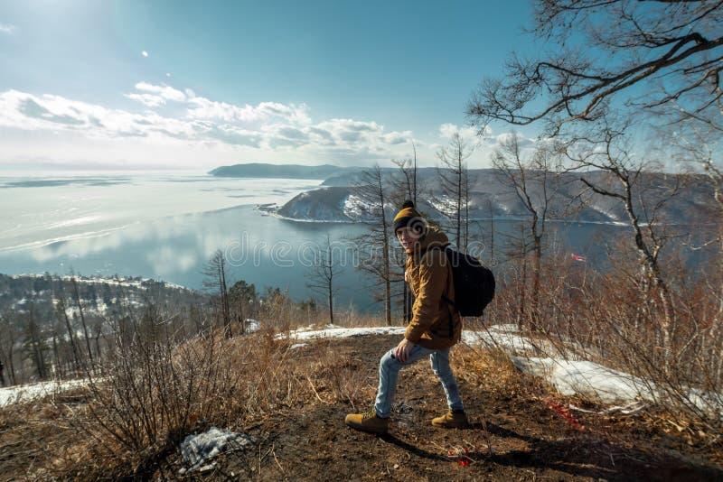 Turystyczny podróżnik z plecaków stojakami na górze i spojrzeniami przy pięknym widokiem jeziorny Baikal Styczeń 33c krajobrazu R obrazy stock