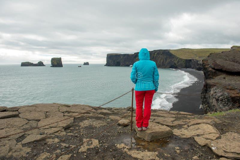 Turystyczny podziwia Dyrholaey półwysep i Atlantyk ocean, Iceland zdjęcia royalty free