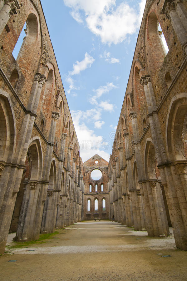 Tuscan Church Ruins. Ruins of a Church in Tuscany, Italy with Dramatic Clouded Sky and Lone Tourist stock image