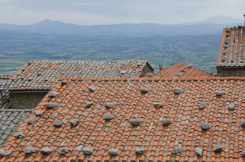 Tuscan Tile Roofs. The terra cotta tile roofs of Tuscany pictured here are sometimes reinforced with large stones placed upon them to keep the winds from stock image