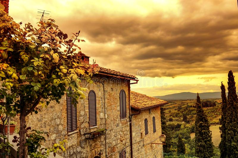 Tuscan view from San Gimignano at sunrise. Tuscan view with warm colors and typical italian building from San Gimignano at sunrise stock image