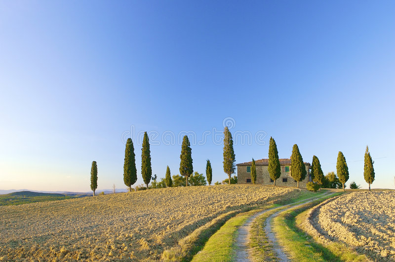 Tuscan villa on a hill in Italy. Typical Tuscan landscape in the hills with a blue sky royalty free stock image