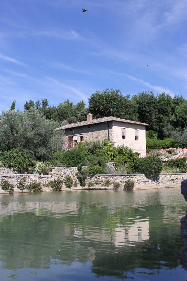 Tuscan Villa on a lake. An old Tuscan villa by a lake surrounded by woodland stock photography
