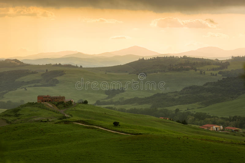 Tuscany krajobraz z domem wiejskim i koloru żółtego niebem, Pienza, Włochy zdjęcie stock