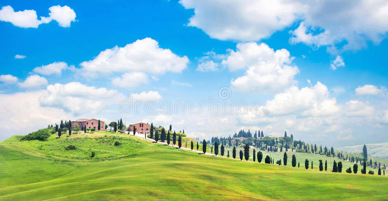 Tuscany landscape with houses on a hill. Scenic Tuscany landscape with typical farm houses on a hill in Val d'Orcia, Italy stock image