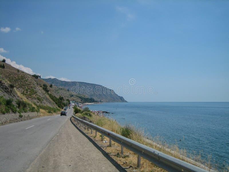 Tussen het overzees en de heuvelsweg aan de kusttoevlucht op een hete Zonnige dag royalty-vrije stock afbeeldingen
