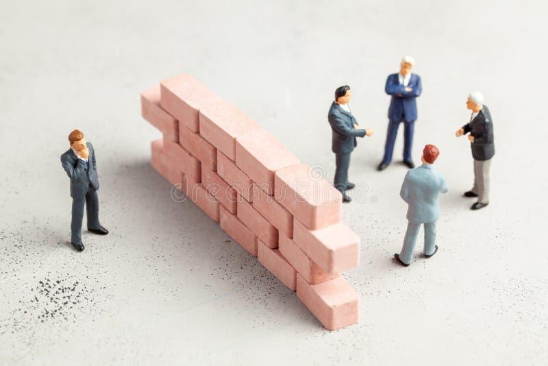 Tussen zakenlieden is een muur van bakstenen, het probleem in mededeling De toegang tot geheime onderhandelingen of regelingen is royalty-vrije stock afbeelding