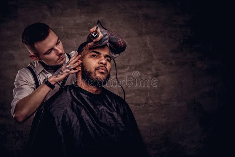 Tut altmodischer Fachmann tätowierter Friseur einen Haarschnitt einen Afroamerikanerkunden an auf der Dunkelheit gemasert stockfotos