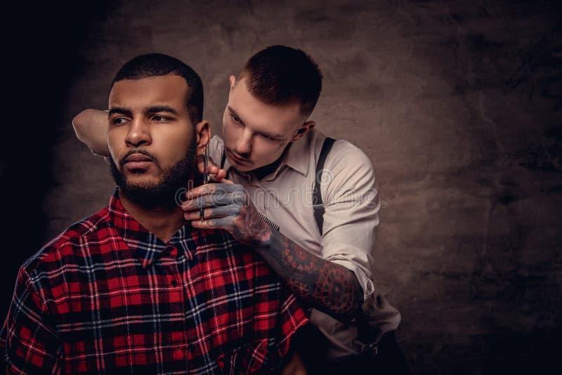 Tut altmodischer Fachmann tätowierter Friseur einen Haarschnitt einen Afroamerikanerkunden an auf der Dunkelheit gemasert lizenzfreies stockbild