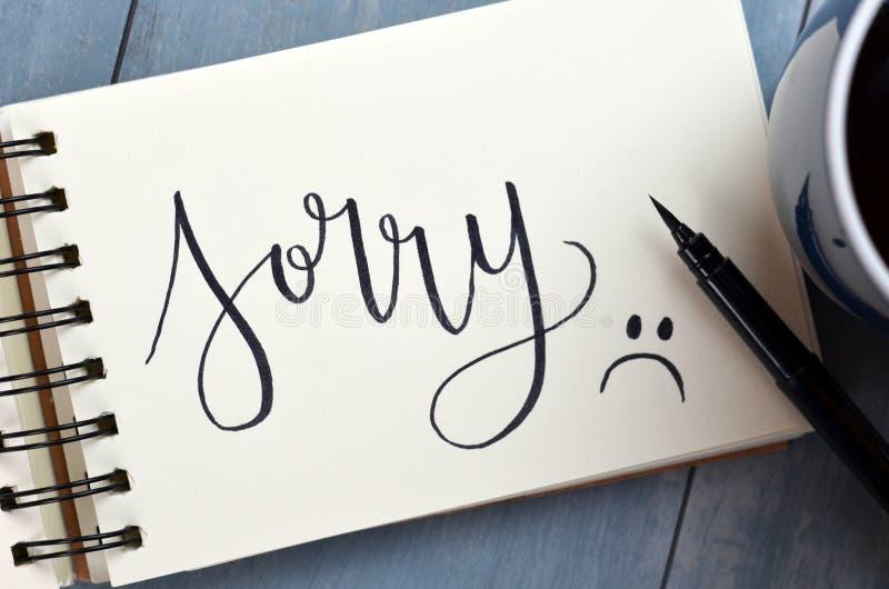 TUT MIR LEID hand-mit Buchstaben gekennzeichnet im Notizblock stockfotografie
