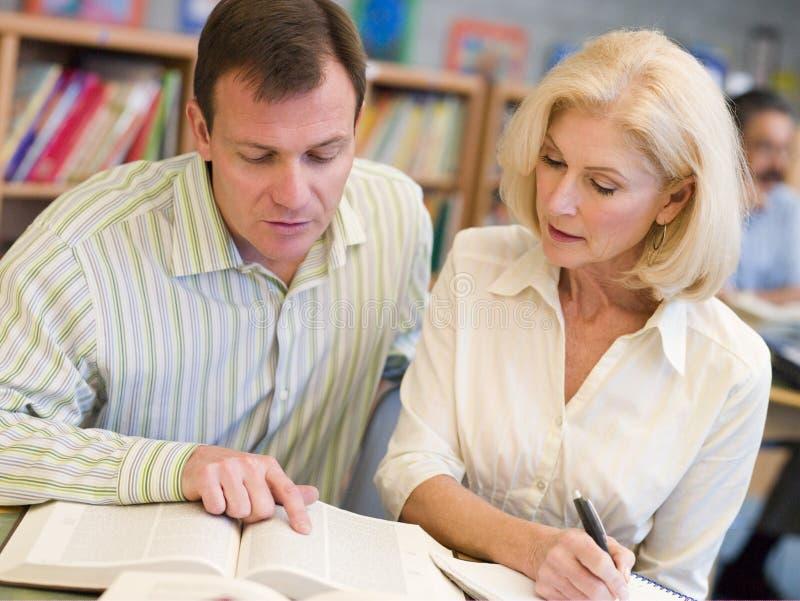 Tutor a ajuda do estudante maduro na biblioteca foto de stock royalty free
