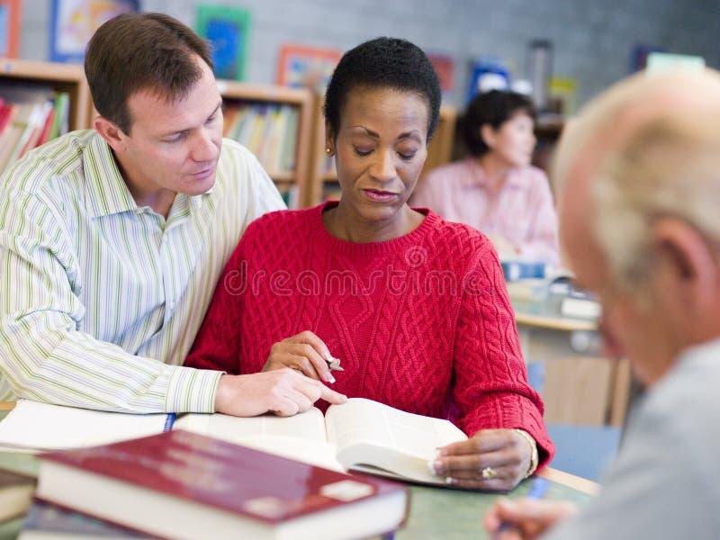 Tutor a ajuda do estudante maduro na biblioteca imagens de stock
