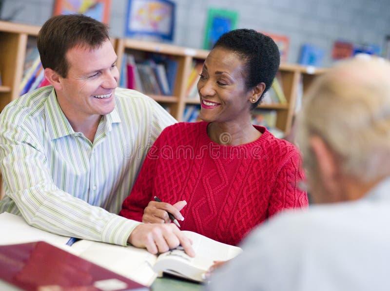 Tutor a ajuda do estudante maduro na biblioteca fotos de stock royalty free