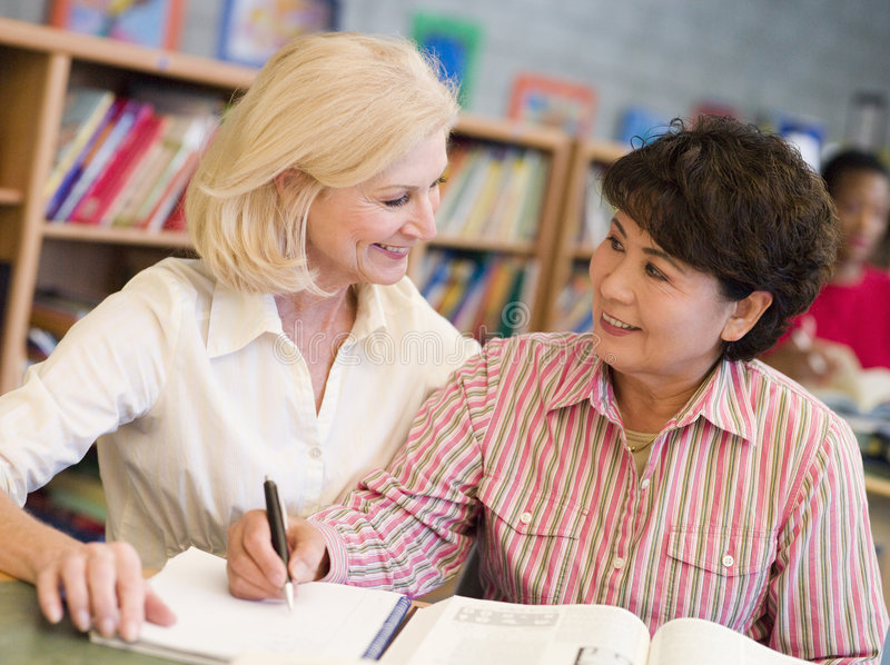 Tutor assisting mature student in library stock photography