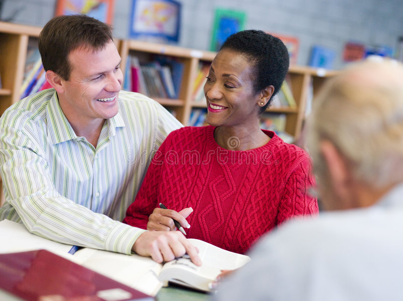 Tutor assisting mature student in library royalty free stock photos