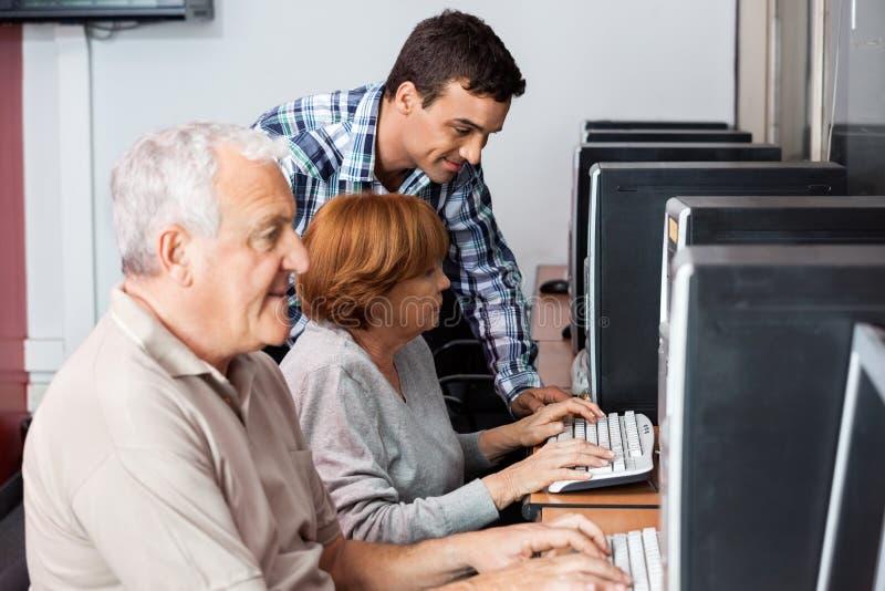 Tutor Assisting Senior Woman, wenn Computer verwendet wird stockfoto
