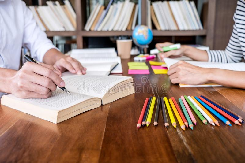 Tutor books with friends, Young students campus or classmates he. Lps friend catching up workbook and learning tutoring in classroom practice preparing exam to royalty free stock image