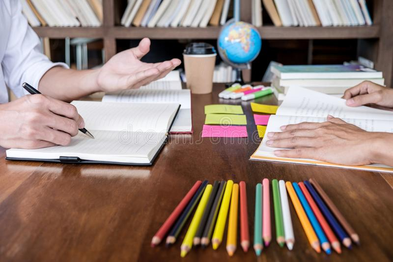 Tutor books with friends, Young students campus or classmates helps friend catching up workbook and learning tutoring in classroom. Practice preparing exam to royalty free stock photography