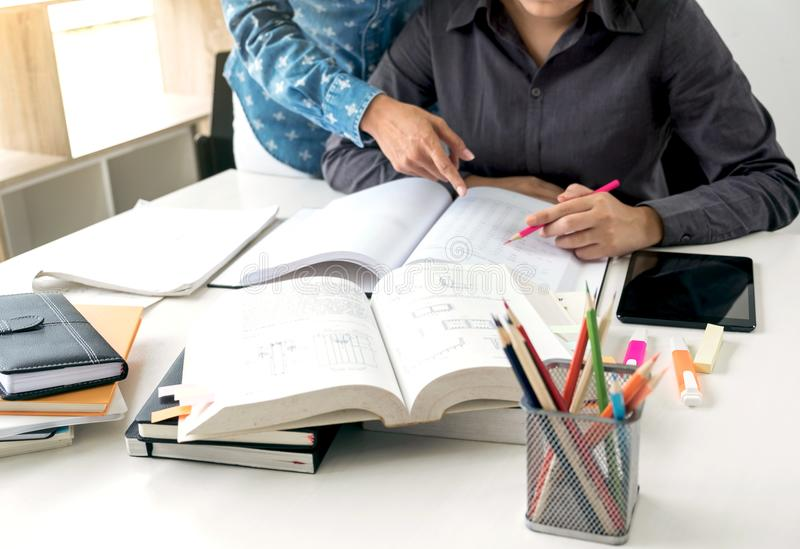 Tutor books with friends, Young students campus or classmates. Helps friend catching up workbook and learning tutoring in classroom, teaching, learning, People stock photography