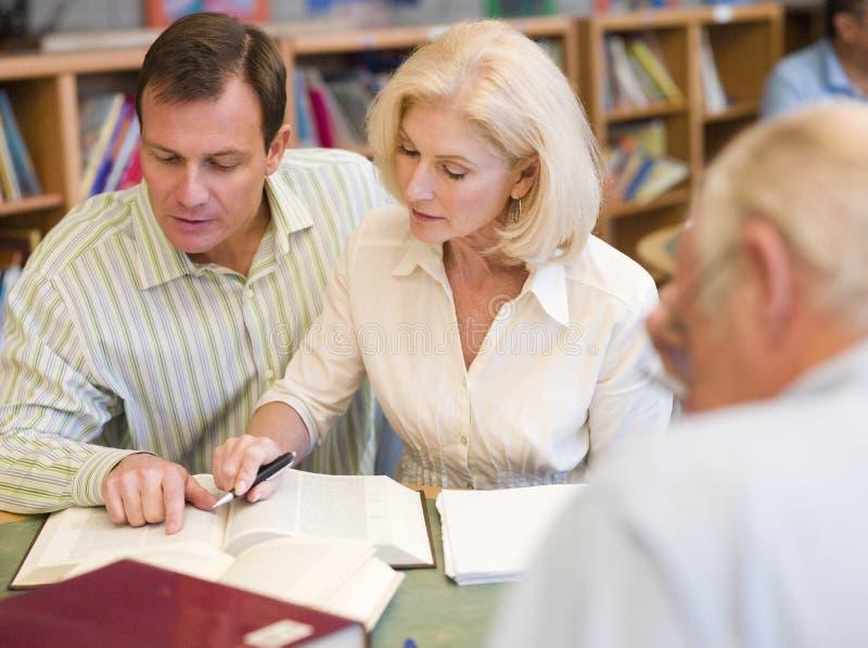 Tutor die Unterstützung des fälligen Kursteilnehmers in der Bibliothek lizenzfreies stockfoto