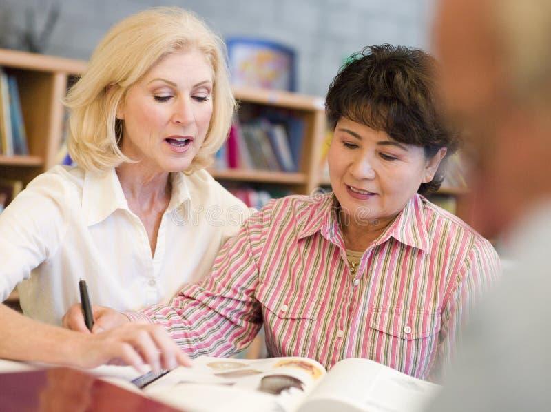 Tutor die Unterstützung des fälligen Kursteilnehmers in der Bibliothek lizenzfreies stockbild