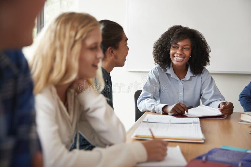 Tutor fêmea Sitting At Table da High School com os alunos que ensinam a classe das matemáticas imagem de stock