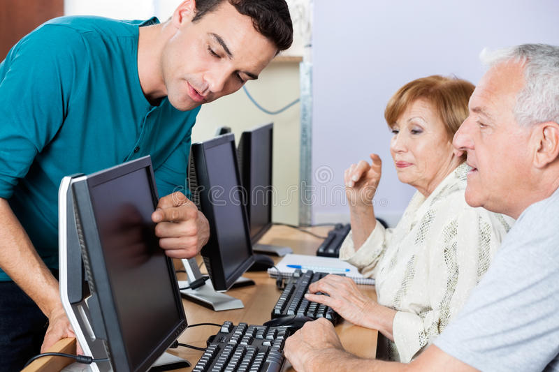 Tutor Guiding Senior Students In Using Computer At Classroom royalty free stock image