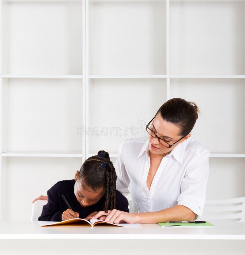 Tutor helfendes Schulmädchen lizenzfreie stockbilder